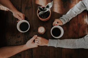 Couple holding hands on table while drinking coffee