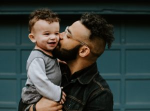 Father kissing his toddler son