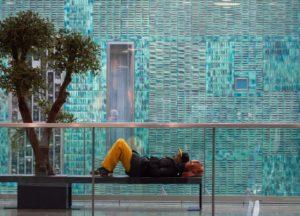 Photo of homeless man sleeping on bench on the street